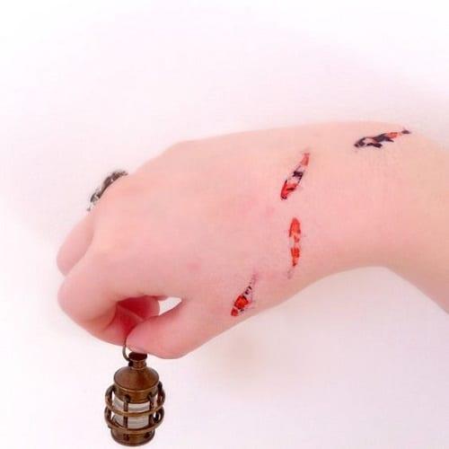 Tiny Koi Tattoo On Hand