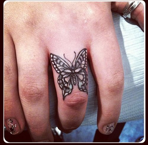 Small Butterfly on Middle Finger Tattoo