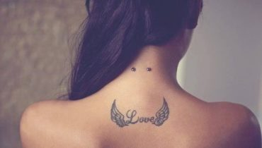 Winged-Love-Word-Tattoo-On-Upper-Back-And-Surface-Nape-Piercing.jpg