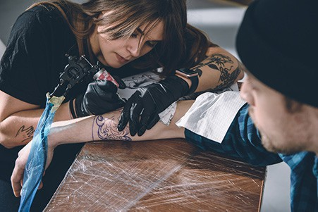 tattoo artist giving a tattoo