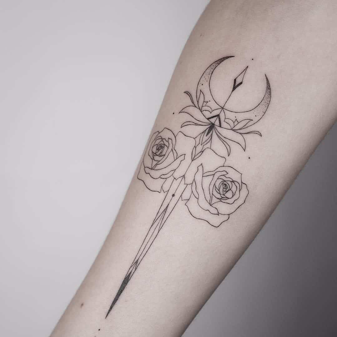 moon and dagger tattoo on arm