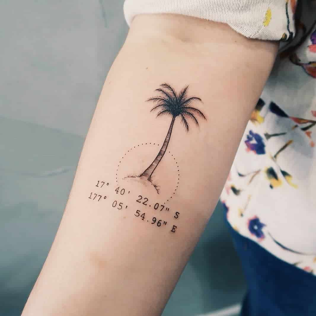 palm tree and coordinates wrist tattoo