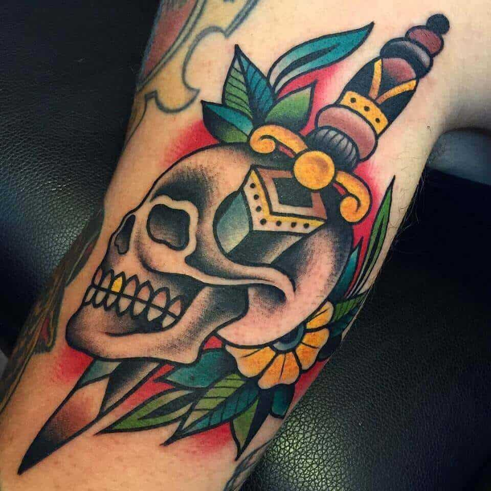 skull and dagger tattoo on arm