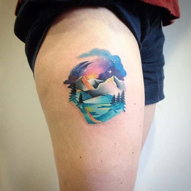 watercolor mountain tattoo on thigh