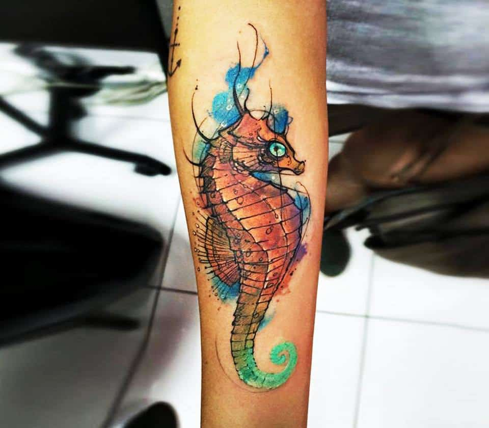 watercolor seahorse tattoo on arm