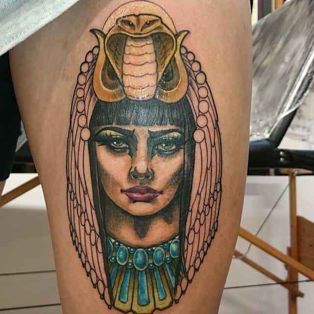 colored egyptian tattoo on thigh